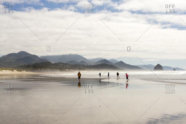 Distant people running on beach