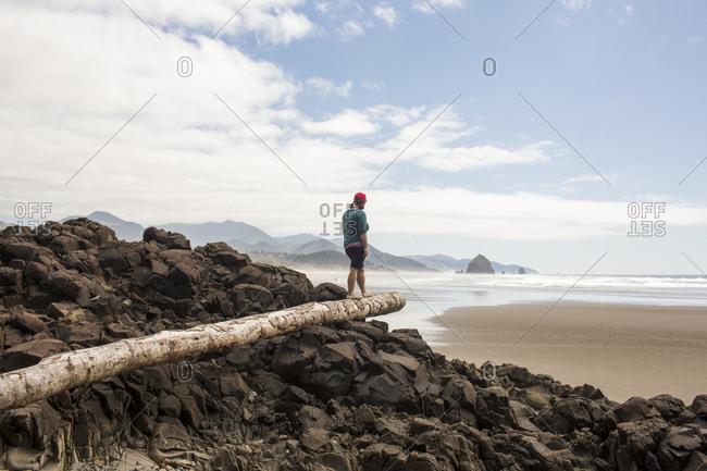 Caucasian woman balancing on log on rocks at beach