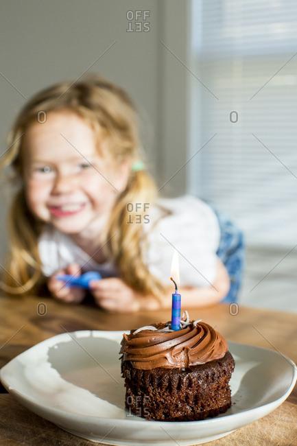 Happy Caucasian girl near birthday cupcake