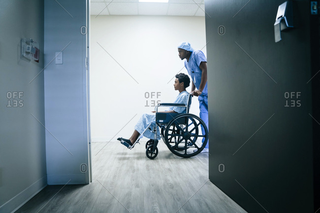 Nurse pushing boy in wheelchair