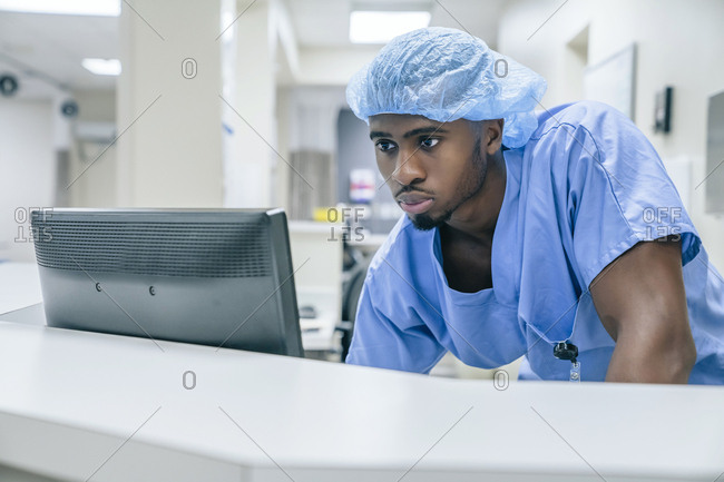 Black doctor using computer in hospital