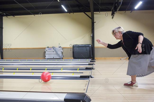 Caucasian woman releasing bowling ball in lane