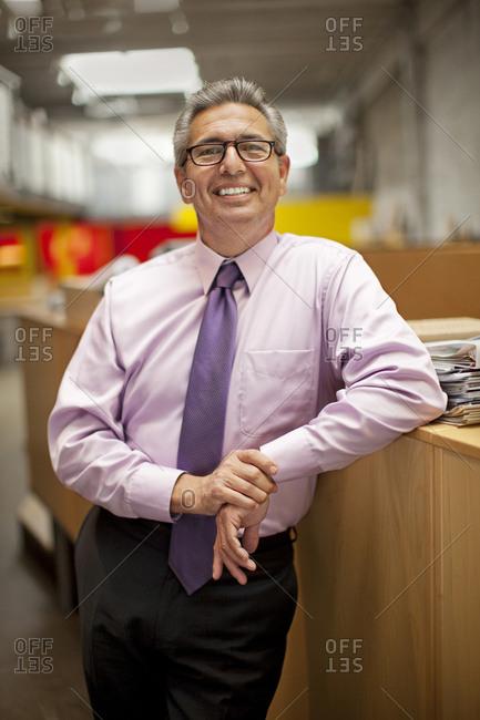 Portrait of smiling Hispanic businessman leaning on desk