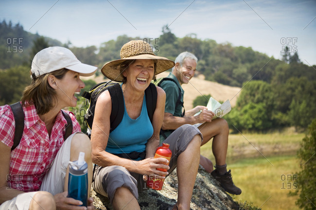 Hikers siting on rock and laughing