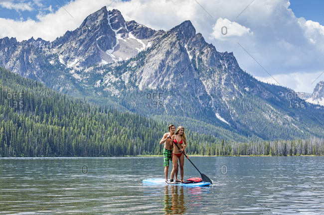Caucasian couple on paddleboard in lake