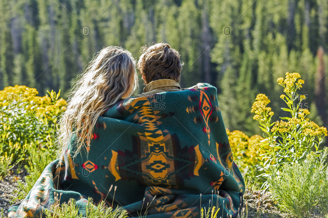 Caucasian couple wrapped in blanket admiring scenic view of landscape