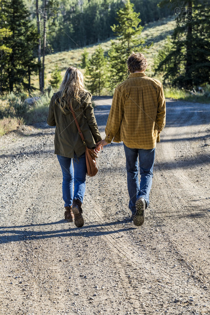 Caucasian couple walking on dirt road holding hands