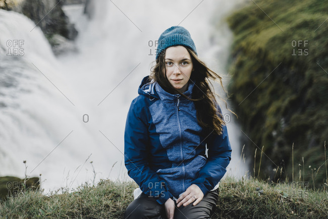 Portrait of serious Caucasian woman sitting near waterfall