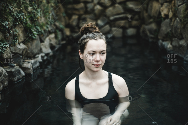 Caucasian woman swimming in pond