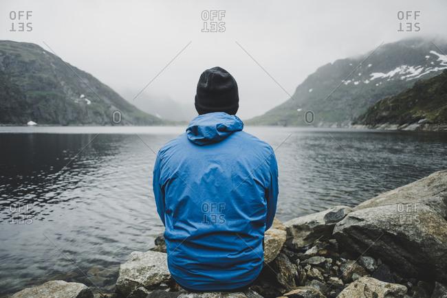 Caucasian man sitting on rocks admiring lake