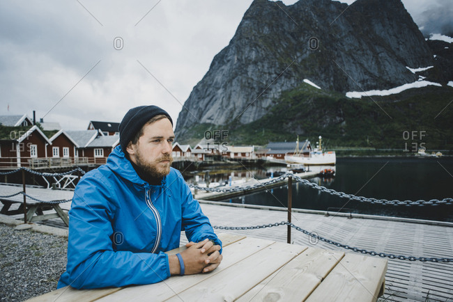 Pensive Caucasian man sitting at table at waterfront