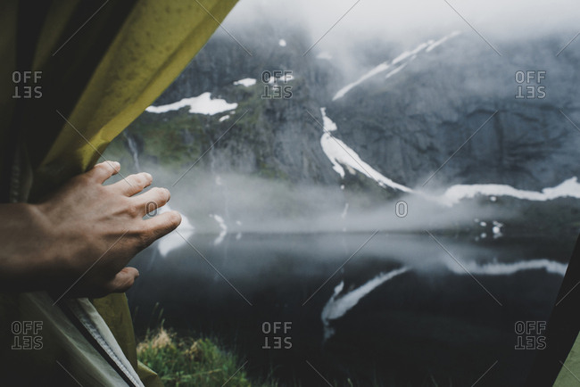 Hand opening tent flap near foggy river