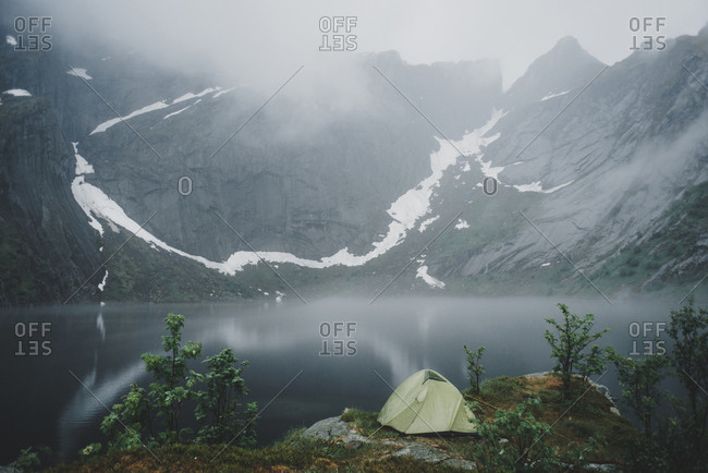 Camping tent near river in fog