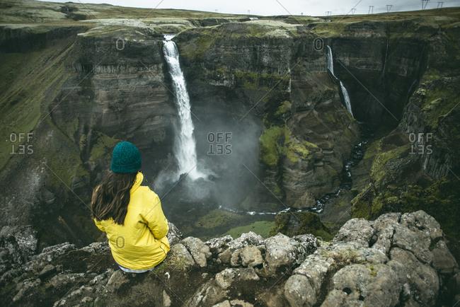Caucasian woman sitting on cliff admiring waterfalls
