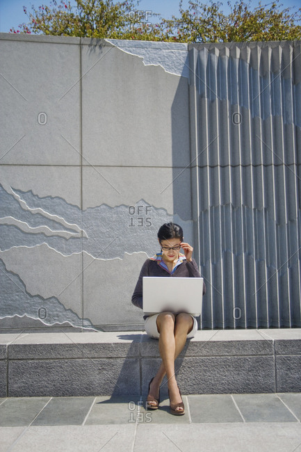 Asian businesswoman sitting on concrete wall using laptop
