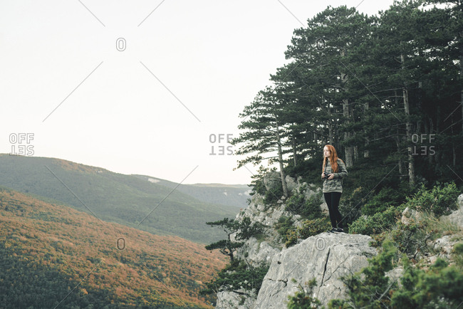 Caucasian woman standing on rock admiring scenic view of landscape