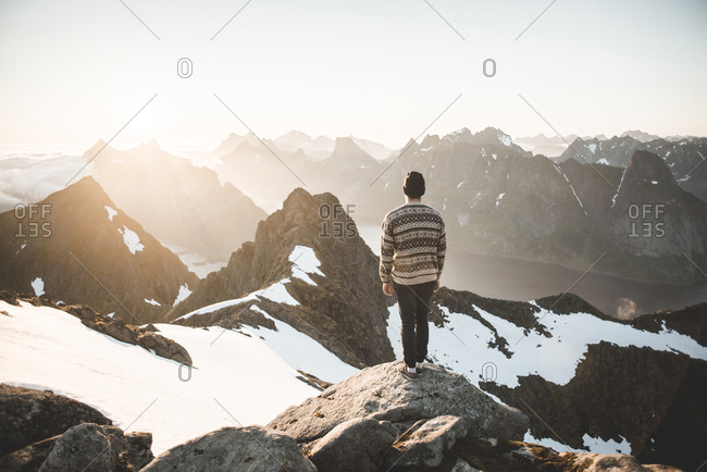 Caucasian man standing on rock admiring scenic view of mountain lake