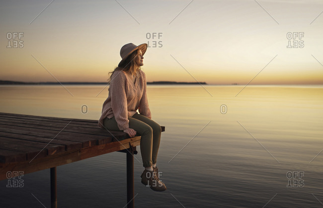 Caucasian woman sitting on dock of lake admiring sunset