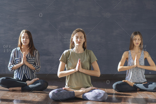 Caucasian women meditating in yoga class