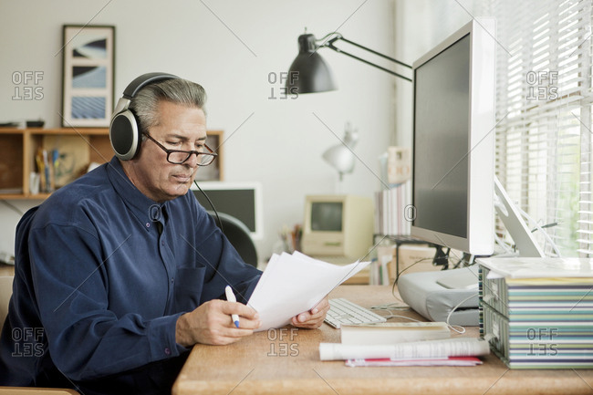 Hispanic businessman reading paperwork and listening to headphones