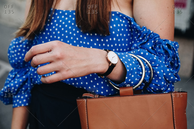 Close-up of a woman wearing a watch and holding a purse