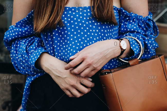Woman wearing a blue polka dot off the shoulder blouse and carrying a purse