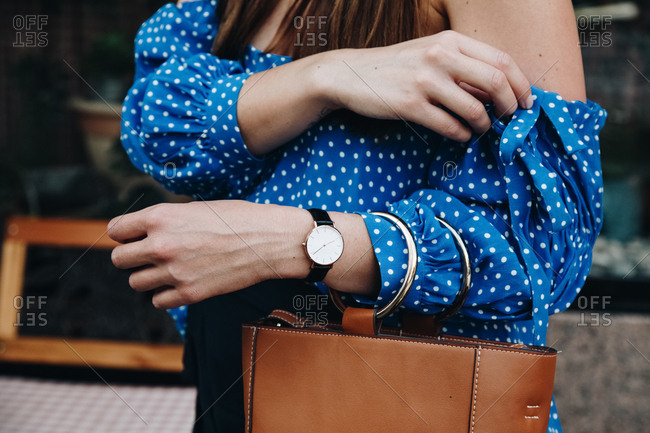 Woman wearing a watch and pulling on her sleeve