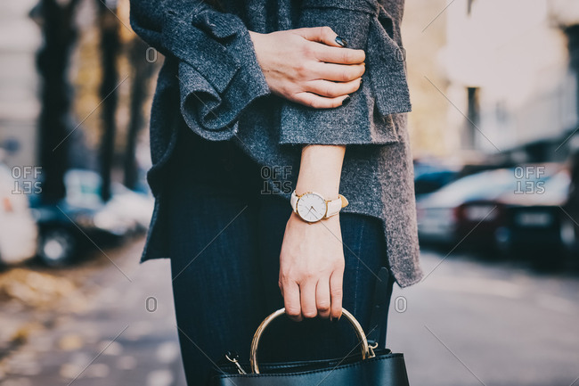 Woman wearing a watch and holding a purse