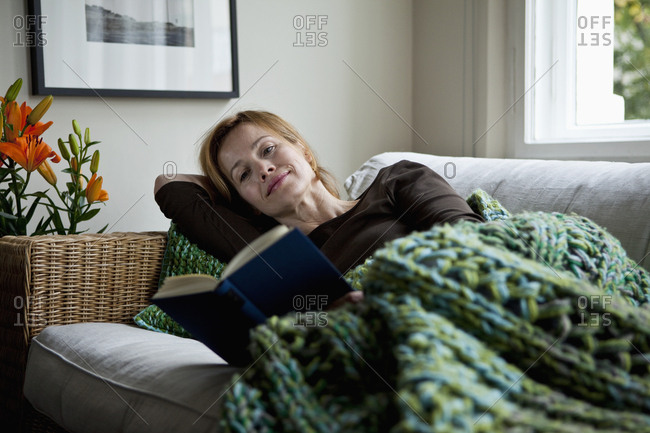 A woman reading a book while reclining on a sofa