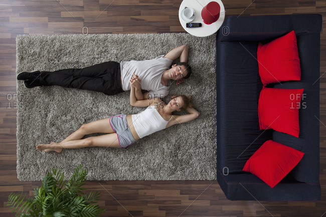A couple lying on a living room rug, holding hands and sleeping, overhead view