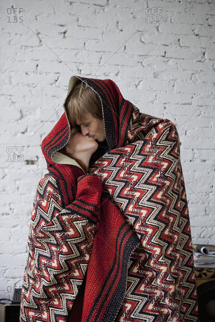 A couple kissing while wrapped in a blanket