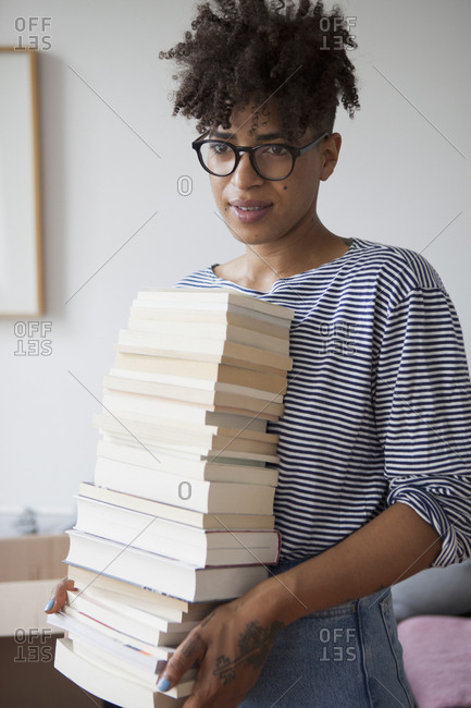 Young woman carrying stack of books at home