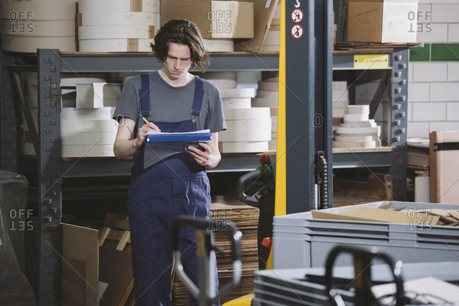 Young manual worker in coveralls writing notes in warehouse