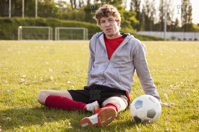 Portrait of young soccer player resting on field