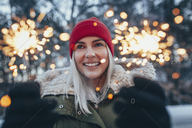 Happy woman holding sparklers during winter