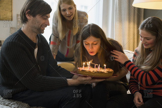 Family looking at young woman blowing out birthday candles at home