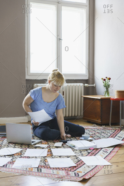Woman doing paperwork while sitting on carpet at home