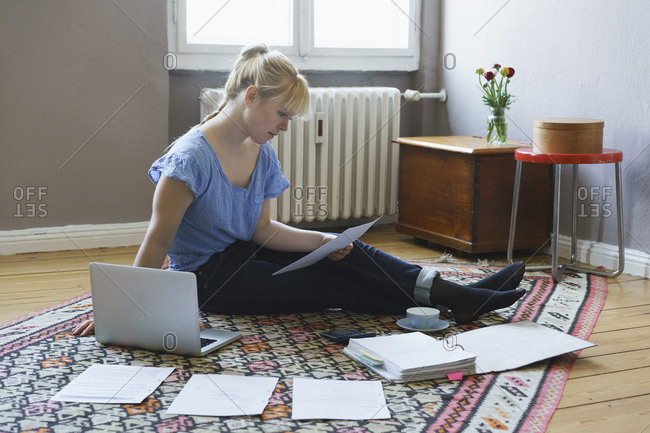 Woman using laptop while doing paperwork at home