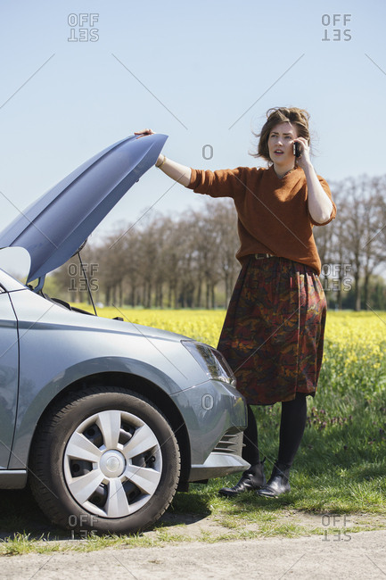Young woman communicating on mobile phone while standing by broken down car