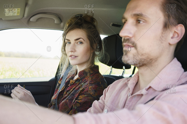 Man driving while sitting besides woman in car