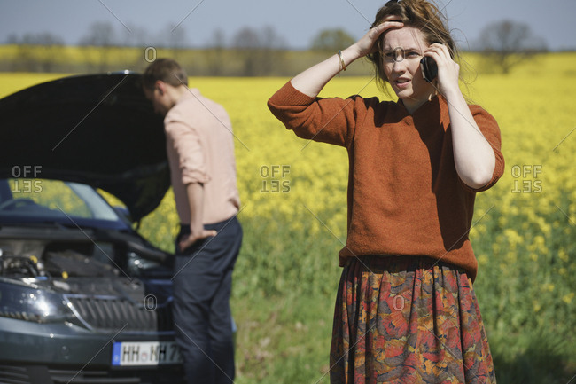 Worried woman talking on phone while man repairing car in background on sunny day