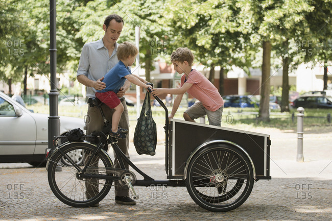 Boys playing on bicycle by father standing on street