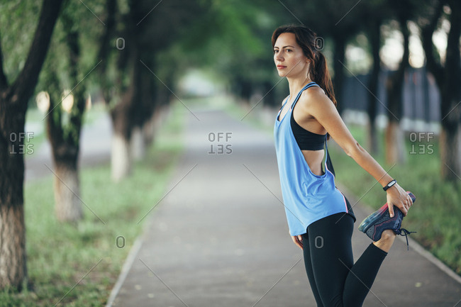 Side view of beautiful woman stretching on footpath at park