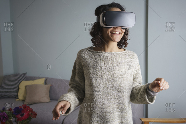 Happy woman using virtual reality headset while standing in living room