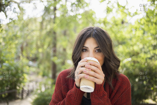 Portrait of beautiful woman drinking from disposable glass at park