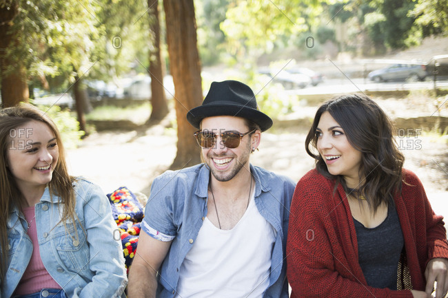 Happy male and female friends sitting on bench in park