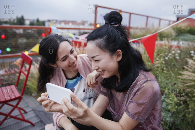 Happy woman looking at female friend using smart phone on patio