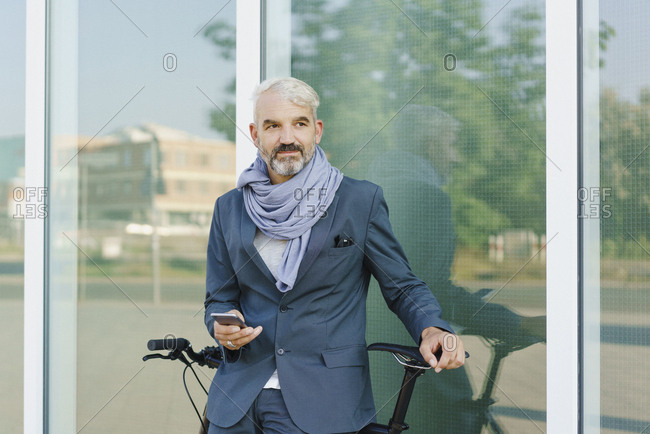 Businessman with bicycle holding smart phone while standing against glass wall