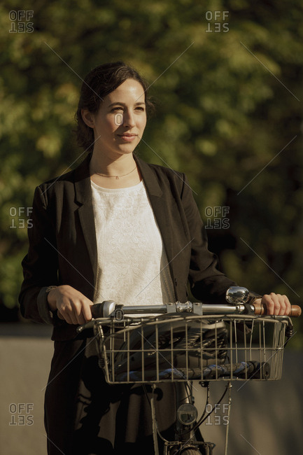Thoughtful businesswoman looking away while standing with bicycle on sunny day