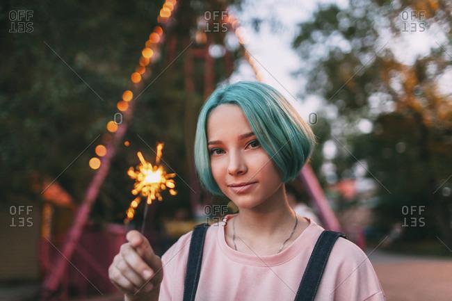 Portrait of teenage girl holding illuminated sparkler